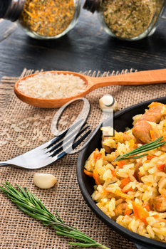 Freshly prepared tasty pilaf in a pan with seasonings on a table close-up