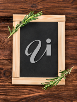 Empty menu with branches of rosemary on a wooden background top view