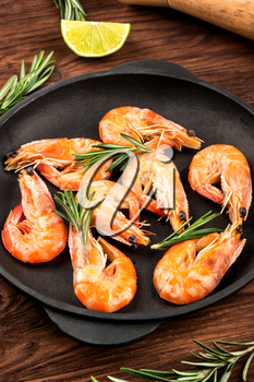 Portion pan with fried shrimp and rosemary on a wooden background close up