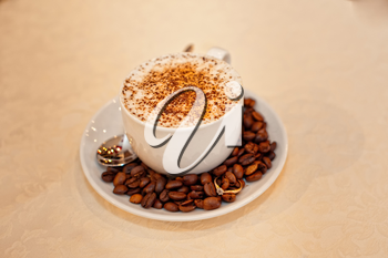 Cup of coffee. Coffee grains was scattered on a saucer and in them the wedding ring are hid.