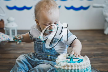 Little boy eats with his hands on the cake.