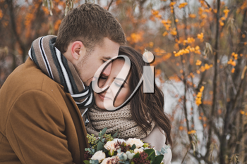 Portrait of a young couple in winter outfits among the branches of sea buckthorn.