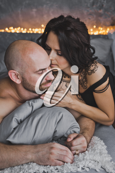 Girl tenderly kisses a bald man on the cheek.