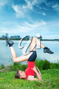 Girl athlete is pushed on one hand on a summer evening in the park by the river with views of the city. Lifestyle