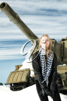brutal girl stands amid battle tank