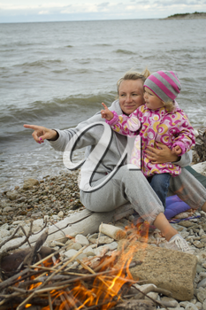 mother and daughter at the sea in the fall sitting around the campfire .