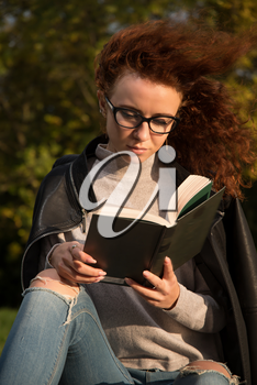 red-haired girl with book in hand in park