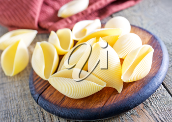 raw pasta on the wooden board and on a table