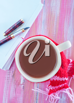 cocoa drink and sheets for note on a table