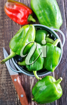 green pepper in metal bowl and on a table