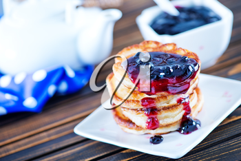 pancakes with jam on plate and on a table