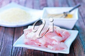 flour, raw egg and raw fish on a table