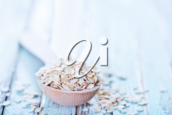 raw oat flakes in spoon and on a table