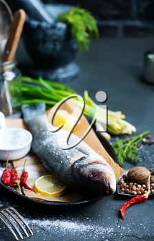 raw fish with lemon and aroma spice on a table