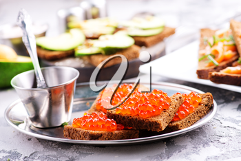 bread with red salmon caviar on a table