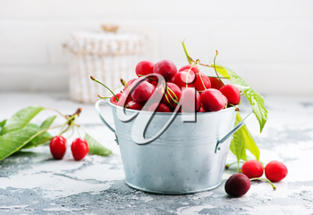 fresh cherry in metal bowl and on a table