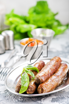 raw sausages with spice on the metal plate