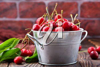 red cherry in bowl and on a table