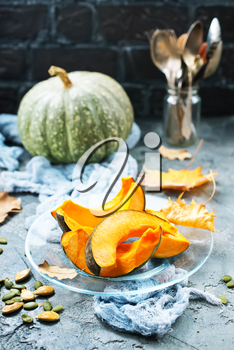 raw pumpkin on plate and on a table