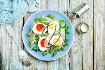 boiled eggs with red salmon caviar, salad on plate