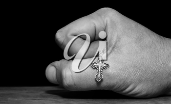 Black and white image of a hand with a cross on a dark background