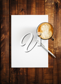 Mock-up for branding identity on vintage wooden table background. Blank letterhead, coffee cup and pen. Mock-up for design presentations and portfolios. Top view.