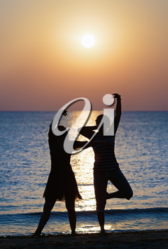 Two girls dancing at sunset on a background of the sea. Focus on models. Shallow depth of field. Toned image.
