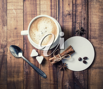 Coffee and spices. Coffee cup, cinnamon sticks, coffee beans, anise, sugar, spoon and coasters on vintage wooden background. Top view.