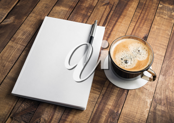 Photo of blank closed book, pencil and coffee cup on wooden table background. Responsive design mockup. Stationery elements. Template for placing your design.