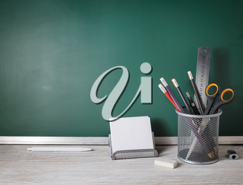 Blank school stationery over green blackboard background. Education concept.