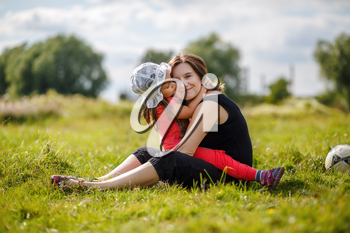 Mother and daughter are hugging. Mom and child girl sitting on grass outdoors. Happy loving family. Selective focus.