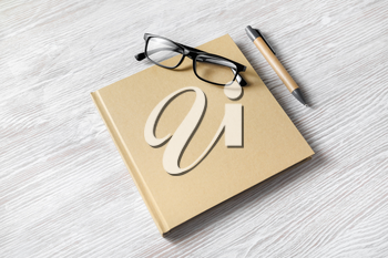 Photo of closed blank square book, glasses and pen on light wooden background. Template for placing your design.