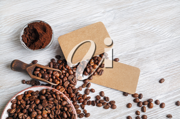 Coffee beans, blank kraft business cards and coffee ground on light wooden background.