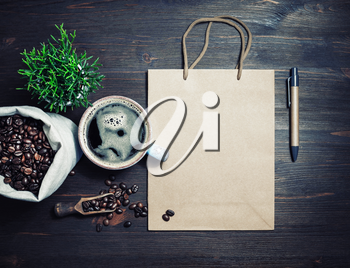 Kraft paper bag, coffee cup, coffee beans, pen and plant on vintage wood table background. Flat lay.