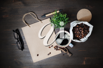 Kraft stationery and coffee. Vintage paper bag, coffee cup, coffee beans, glasses, pen and plant on wood table background. Flat lay.