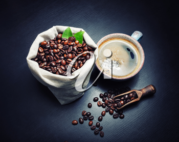 Delicious fresh coffee. Coffee cup and roasted coffee beans on black wooden kitchen table background.