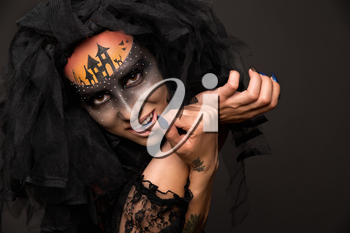 Halloween devil's bride. Portrait of young woman in dark artistic image with scary makeup, veil and terrible picture on her forehead.