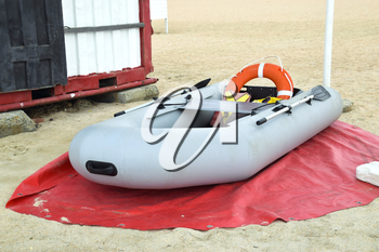 Inflatable Rescue Boat. Gray inflatable boat on the beach in the sand.