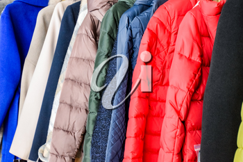 Coats and jackets on hangers in the store. Sale of outerwear