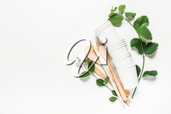 Wooden fork, spoon, knife, tube, paper cups on a white background. The concept of recycling, eco, planet conservation, zero waste