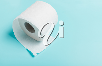 Close-up of white toilet paper on blue background. Top view. The concept of hygiene, cleanliness