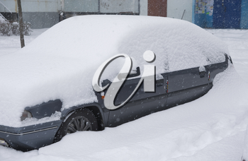 Car under snowdrift. Winter problem scene.