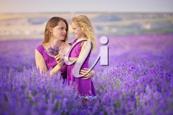 Little girl and mother at meadow of lavender. Family care and nature composition.