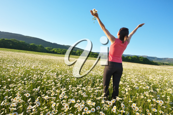 Happy girl in daisy wheel spring flower field. Emotional and nature scene.