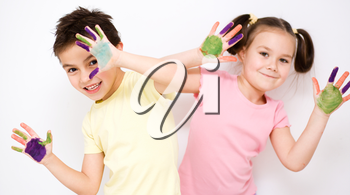 Cute boy and girl showing her hands painted in bright colors