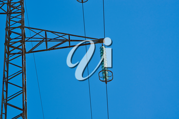 High-voltage tower. Electric powerlines on the blue sky.