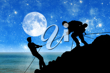 Concept of aid. Silhouette of two climbers helping each other against the backdrop of the sea and the moon at night