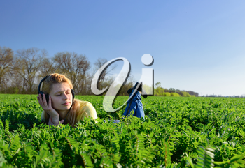 Concept of music. Young woman with headphones listening to music on meadow