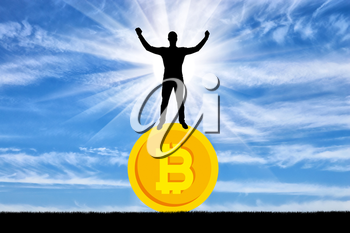 Happy man standing on a coin bitcoin. The concept of success in the crypto currency