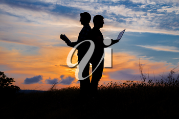 silhouette of a men with laptop and a book on sunset or sunrise background. The idea of the contradictions of the old and new values. The concept of old and modern